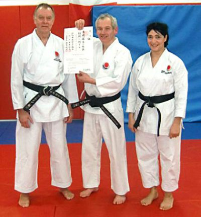 Adrian Thomas (pictured centre) receives his 1st Dan JKA Diploma